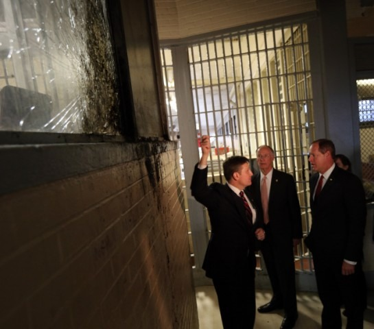 Governor tour of Holman, looking at a shattered window from the recent rebellion.