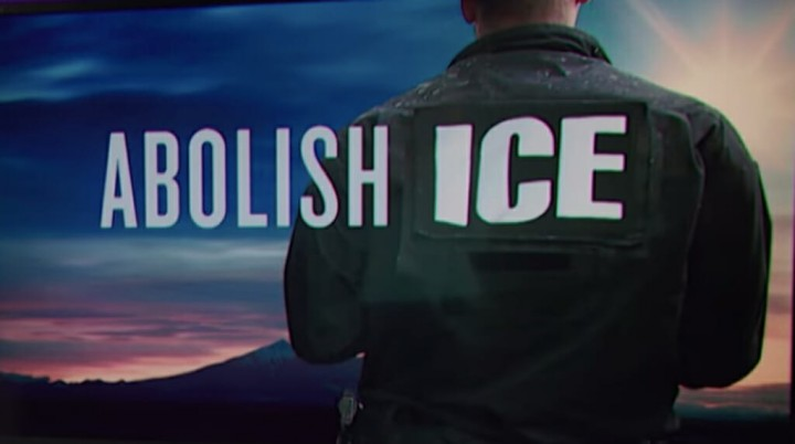 """Abolish ICE across a twilight image and ICE agent, back turned to viewer"