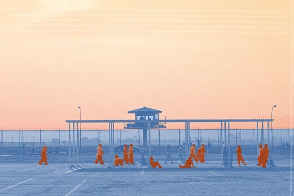 CDCr prison yard, imprisoned people in orange jumpsuits in the foreground